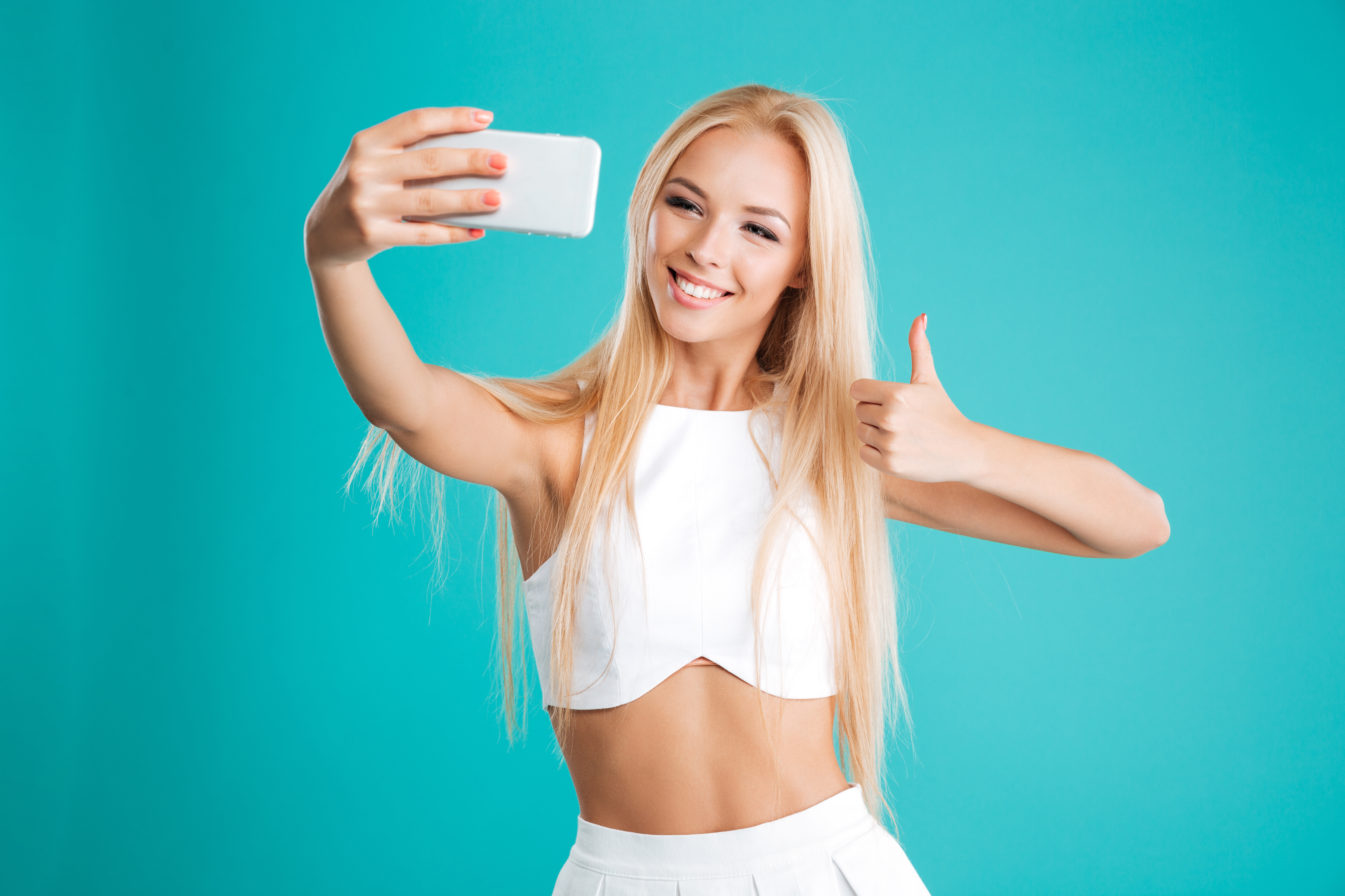 Portrait of a happy smiling girl taking selfie and showing thumb up gesture isolated on the blue background
